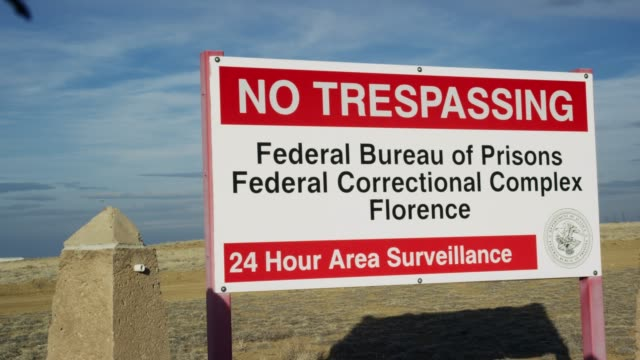 """no trespassing federal bureau of prisons federal correctional complex florence, 24 hour area surveillance"" sign outside of the exterior of the united states penitentiary, administrative maximum facility supermax prison complex in florence, colorado (frem - no trespassing stock videos & royalty-free footage"
