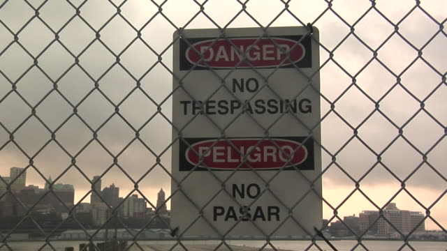 cu, no trespassing sign on chain link fence, manhattan skyline in background, new york city, new york, usa - no trespassing stock videos & royalty-free footage
