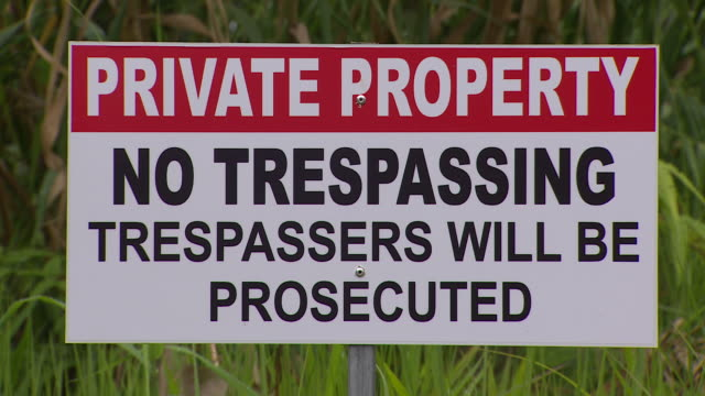 no trespassing sign on grassy area of village of naviavia, fiji. - no trespassing stock videos & royalty-free footage
