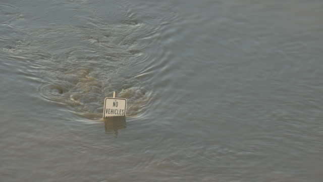 WS  No Vehicles sign, barely visible above Trinity River flood waters, Dallas, Texas