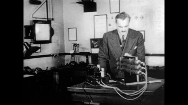 / nobel prize winning physicist arthur compton operates machine to demonstrate the compton effect related to electromagnetic radiation / makes notes... - physik stock-videos und b-roll-filmmaterial