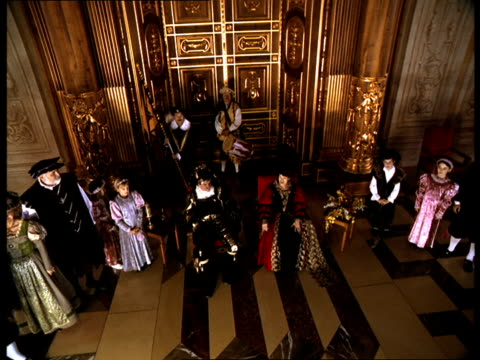 vídeos de stock, filmes e b-roll de nobles surround the king and queen as they sit in the grand hall of a palace. - século xvi