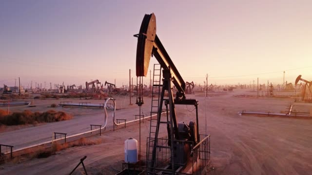 nodding donkey in california oil field at sunset - drone shot - crude oil stock videos & royalty-free footage