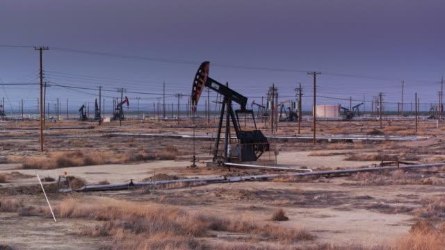 Nodding Donkey Pump Jack in Oil Field at Dusk
