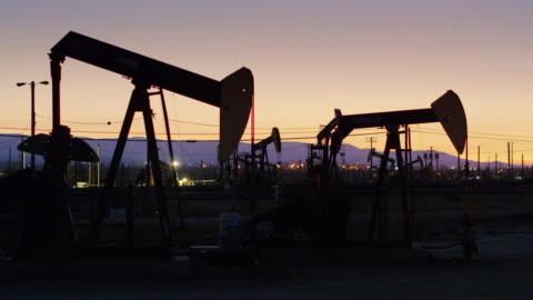 nickande åsna pump jacks silhuett i solnedgången - stigande drone skott - oljepump bildbanksvideor och videomaterial från bakom kulisserna