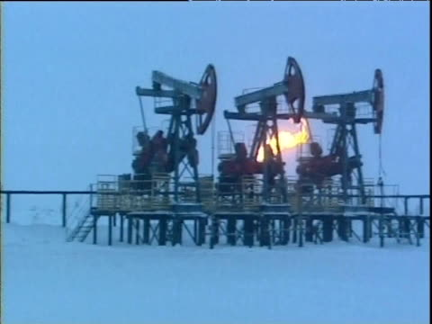 Nodding donkeys drill for oil in snow with large flame Siberia