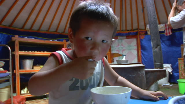 MS Nomad boy eating in yurt / Central-south Mongolia, Central-south Mongolia, Mongolia