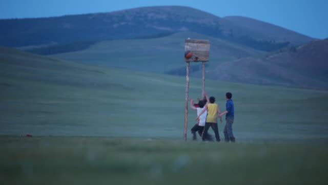 vídeos y material grabado en eventos de stock de ms nomad boys playing basketball / central-south mongolia, mongolia - fundido en negro