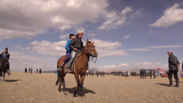 Nomadic boys on horseback in Mongolia at Golden Eagle Festival