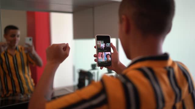 vidéos et rushes de personne non-binaire faisant un appel vidéo utilisant le smartphone à la maison et la danse - rester à la maison expression