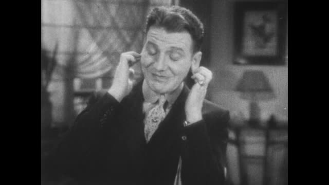 vídeos de stock, filmes e b-roll de 1931 nonchalant smiling man (frank fay) covers ears as gunshot sounds - noise
