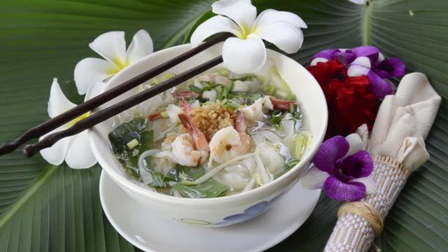 CU Noodle soup with shrimp and decorated with frangipani flower / Mae Nam, Ko Samui, Thailand