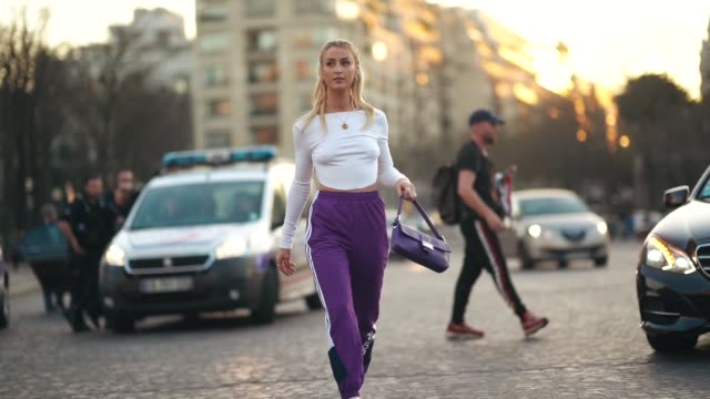 noor de groot wears a necklace, a white crop top, purple adidas sport pants, a purple fendi handbag, white high-heeled sandals, outside rochas,... - street style stock videos & royalty-free footage