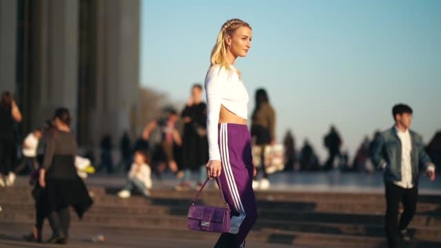Noor De Groot wears a necklace a white crop top purple Adidas sport pants a purple Fendi handbag white highheeled sandals outside Rochas during Paris...