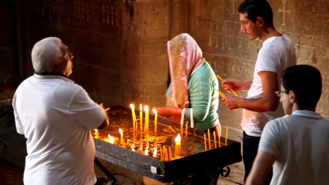 Noravank monastery, believers light votive candles, Armenia
