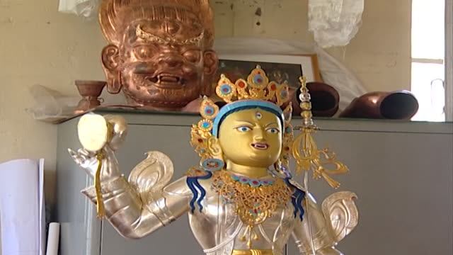norbulingka institute. a statue with gilded face created by artisans at norbulingka which is dedicated to the preservation of tibetan arts. - gambe incrociate video stock e b–roll