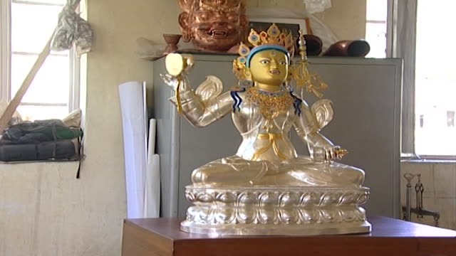norbulingka institute buddhist statue with gilded face created by artisans at norbulingka which is dedicated to the preservation of tibetan arts - cross legged stock videos & royalty-free footage