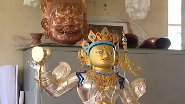norbulingka institute. tilt-down on a buddhist statue created by artisans at norbulingka which is dedicated to the preservation of tibetan arts. - cross legged stock videos & royalty-free footage