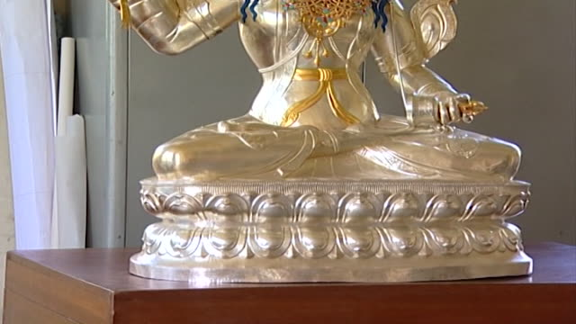 norbulingka institute. tilt-up on a buddhist statue created by artisans at norbulingka which is dedicated to the preservation of tibetan arts. - gambe incrociate video stock e b–roll