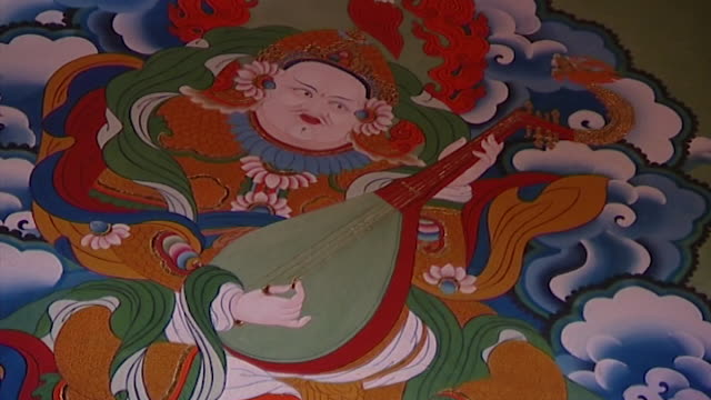 norbulingka institute. view of a buddhist deity with a headdress playing the khushtar or lute in a mural. - headdress stock videos & royalty-free footage