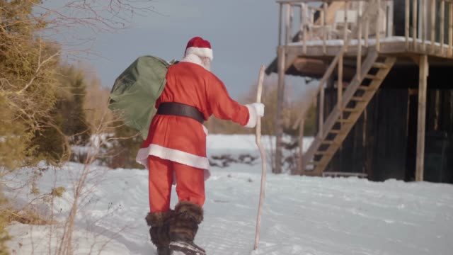nordic santa claus walking towards the house (slow motion) - bag stock videos & royalty-free footage