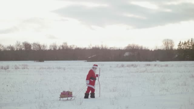 vídeos de stock e filmes b-roll de nordic santa claus walking with presents on seldge (slow motion) - pai natal