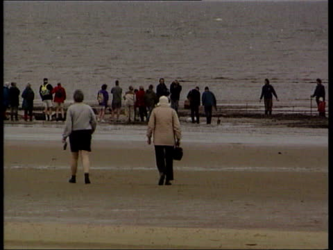 norfolk holme next the sea ext footsteps on beach track people gathered on the beach man excavating remains of tree stump tree stumps sticking out... - footprint stock videos & royalty-free footage