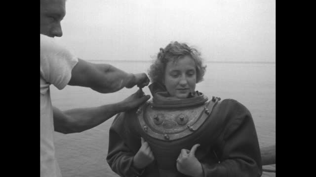 vs norma hanson watches as two men assemble her diving equipment man in captain's hat is probably her husband al hanson the men use wrenches to screw... - diving helmet stock videos and b-roll footage
