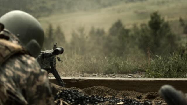 normal speed to super slow motion shot of soldier shooting chain gun; training at firing range. - einzelner mann über 30 stock-videos und b-roll-filmmaterial