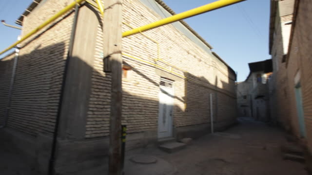 normal street with visible gas pipelines in the residential area of the historic city of bukhara, uzbekistan - bukhara stock videos and b-roll footage