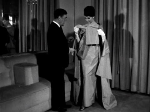 Norman Hartnell inspects a model wearing one of his evening gowns 1961