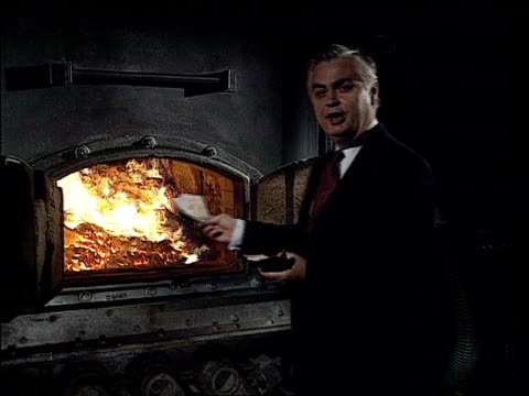 norman lamont i/c sot as burns cash in furnace zoom in too much cash in the system is bad for the economy and so i'm going to burn it cs money... - 1990 1999 stock-videos und b-roll-filmmaterial