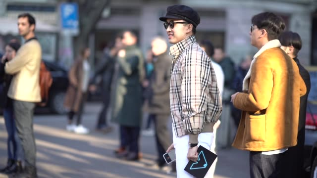 Norman Tan wears a beret hat sunglasses a checked bomber jacket a clutch during Milan Menswear Fashion week Fall/Winter 2018/19 on January 13 2018 in...