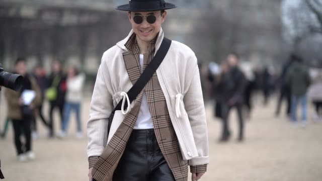 Norman Tan wears a hat sunglasses a white coat over a checked brown blazer jacket black leather pants during Paris Fashion Week Menswear F/W 20192020...