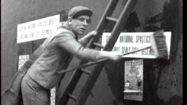 norman wisdom, in character as norman pitkin, putting up posters promoting the national spastics society christmas seals day in a comic way and... - ladder stock videos & royalty-free footage