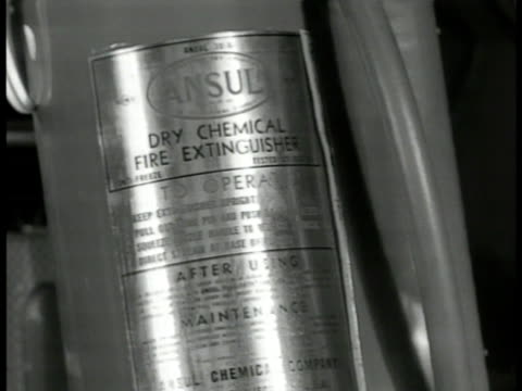 MS 'Norman Wright' pulling out new dry chemical fire extinguisher from box CU 'Ansul' label w/ instructions MS Wright taking extinguisher outside EXT...