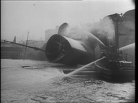 ss normandie capsized in the new york harbor / view of ship on side in icy water / view with top of ship toward camera / tug boat hosing down ship /... - capsizing stock videos & royalty-free footage