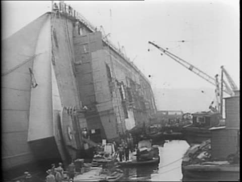 uss normandie sailing up a river / uss normandie wrecked on its side in the water / men walking around the wrecked ship at a port / cranes working... - 1942年点の映像素材/bロール