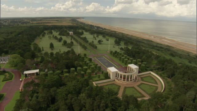 aerial normandy american cemetery and memorial with rows of white grave markers and monument structure on green bluff overlooking omaha beach / colleville-sur-mer, basse-normandie, france - omaha beach stock videos and b-roll footage