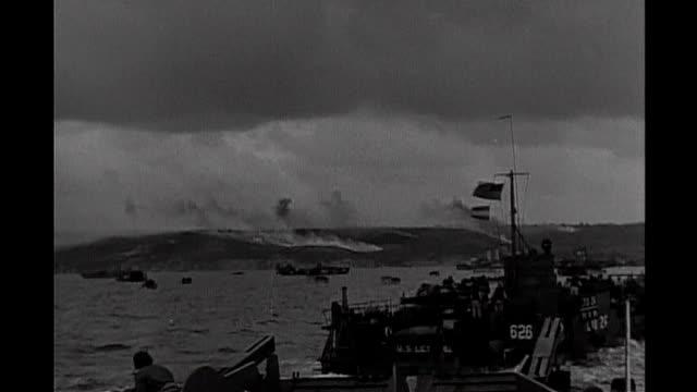 normandy ext b/w archive footage of us landing craft in shallow water of normandy beach allied troops disembarking flotilla of small craft offshore... - 1944 bildbanksvideor och videomaterial från bakom kulisserna