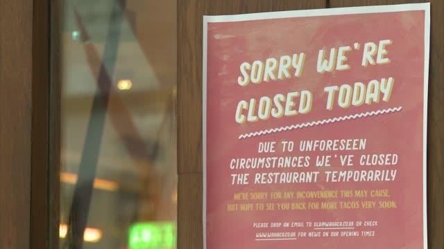 norovirus outbreak at london restaurant chain; london: wahaca logo on window of restaurant sign on door about closure kitchens seen through window... - door chain stock videos & royalty-free footage