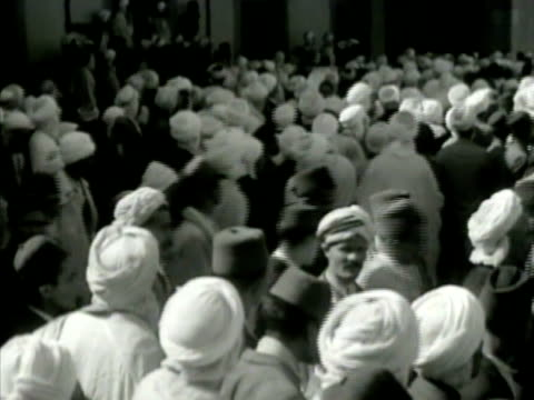 stockvideo's en b-roll-footage met north african natives wearing turbans crowded on street ms two natives walking ws german axis agitator man talking to crowd of natives ms natives... - 1942