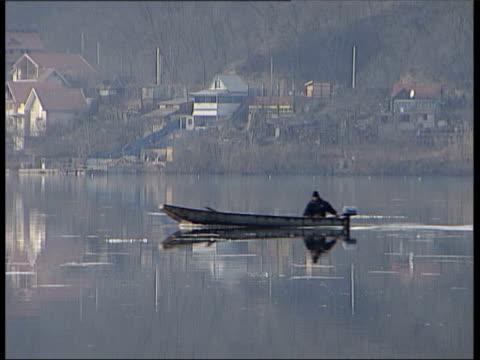 north eastern serbia: danube: ext tgv river as man along past in boat - slobodan milosevic stock-videos und b-roll-filmmaterial