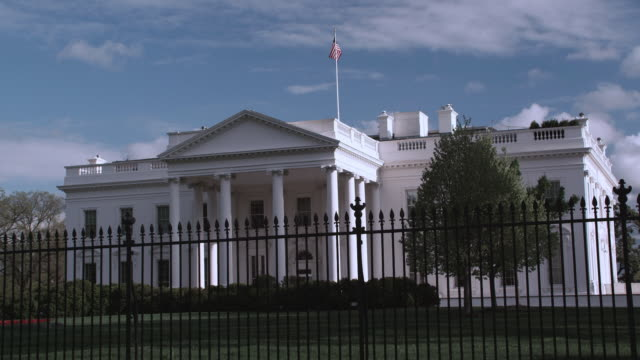 ws north entrance to the white house behind decorative iron fence, tourists walking in front / washington, d.c., united states - 2010年代点の映像素材/bロール