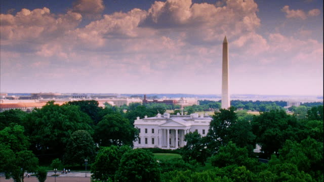 North facade of White House w/ buildings Washington Monument BG lush green trees FG pink tones on clouds obelisk