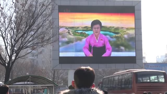 north korea : a woman looks at a photo of north korean leader kim jong un's hand-written letter to citizens shown on her smartphone in pyongyang on... - korean new year stock-videos und b-roll-filmmaterial