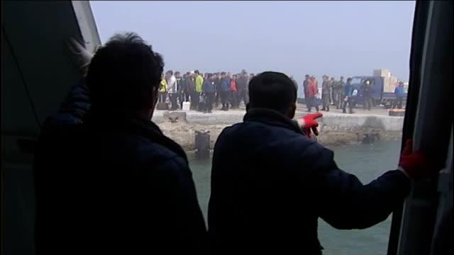 north korea moves midrange missiles to east coast south korea yeonpyeong island back view of two men standing on boat yeonpyeong residents standing... - 2013年 北朝鮮の核実験点の映像素材/bロール