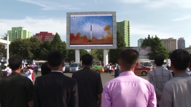 people in pyongyang watch a news report on a test of the intermediaterange hwasong12 on a large screen in front of a station on sept 16 2017 north... - ミサイル点の映像素材/bロール