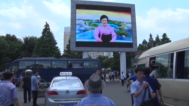 people watch on july 1 a street television in pyongyang reporting on a historic meeting the previous day between us president donald trump and north... - 北朝鮮点の映像素材/bロール