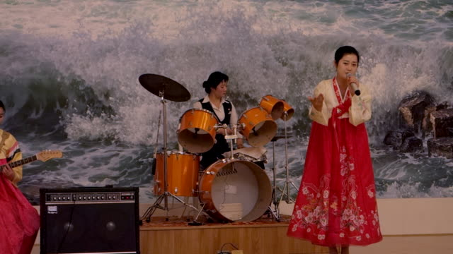 North Korean artists sing songs on stage for tourists